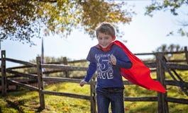 Menino idoso de cinco anos de sorriso que corre com parte externa vermelha do cabo fotografia de stock