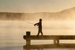 Menino iluminado traseiro que pesca fora de um molhe fotografia de stock