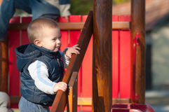 Menino infantil bonito que sorri no campo de jogos Fotografia de Stock Royalty Free
