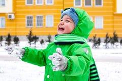 Menino infantil de riso que mantém a neve em suas mãos Fotografia de Stock Royalty Free