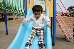 Menino japonês na corrediça Imagem de Stock