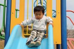 Menino japonês na corrediça Imagens de Stock