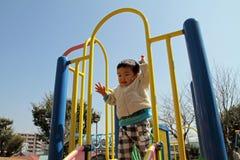 Menino japonês na corrediça Fotos de Stock Royalty Free
