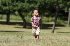 Menino japonês que corre na grama Fotos de Stock