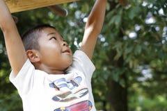 Menino japonês que joga com as barras de macaco foto de stock royalty free
