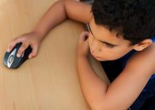 Menino latin pequeno que trabalha em um computador Foto de Stock