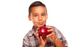 Menino latino-americano adorável que come um grande Apple vermelho imagens de stock royalty free