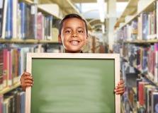 Menino latino-americano de sorriso que guarda a placa de giz vazia na biblioteca Fotos de Stock
