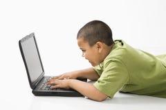 Menino latino-americano no computador. foto de stock