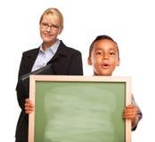 Menino latino-americano que prende a placa e o professor em branco de giz Imagem de Stock Royalty Free