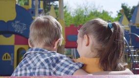 Menino louro adorável e uma menina bonita que senta-se no banco na frente do aperto do campo de jogos Um par crianças felizes vídeos de arquivo