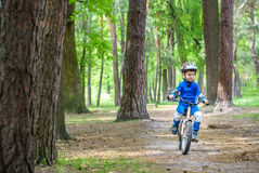 Menino louro bonito feliz da criança que tem o divertimento sua primeira bicicleta no dia de verão ensolarado, fora criança que f Fotos de Stock Royalty Free