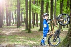 Menino louro bonito feliz da criança que tem o divertimento sua primeira bicicleta no dia de verão ensolarado, fora criança que f Imagem de Stock Royalty Free
