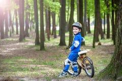 Menino louro bonito feliz da criança que tem o divertimento sua primeira bicicleta no dia de verão ensolarado, fora criança que f Fotografia de Stock