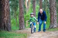 Menino louro bonito feliz da criança que tem o divertimento sua primeira bicicleta no dia de verão ensolarado, fora criança que f Foto de Stock Royalty Free