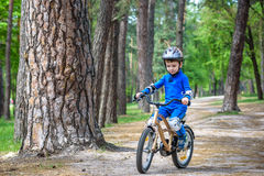Menino louro bonito feliz da criança que tem o divertimento sua primeira bicicleta no dia de verão ensolarado, fora criança que f Fotografia de Stock Royalty Free