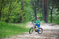 Menino louro bonito feliz da criança que tem o divertimento sua primeira bicicleta no dia de verão ensolarado, fora criança que f Imagens de Stock