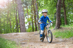 Menino louro bonito feliz da criança que tem o divertimento sua primeira bicicleta no dia de verão ensolarado, fora criança que f Imagem de Stock