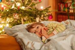 Menino louro bonito pequeno que dorme sob a árvore de Natal Imagem de Stock