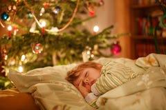 Menino louro bonito pequeno que dorme sob a árvore de Natal Imagens de Stock