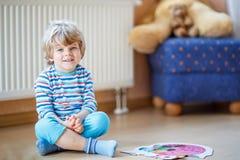 Menino louro bonito pequeno que joga com jogo do enigma em casa Imagem de Stock Royalty Free