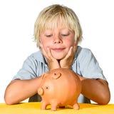 Menino louro com banco piggy imagens de stock royalty free