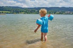 Menino louro com os flutuadores que mergulham seus pés em um lago altitude imagem de stock