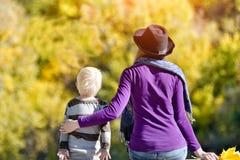 Menino louro com sua mãe no chapéu que senta-se no banco de rio Fotos de Stock Royalty Free