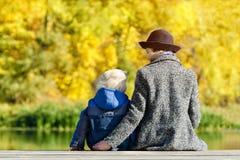 Menino louro e sua mãe no chapéu que senta-se na doca Vista traseira Imagens de Stock Royalty Free