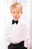 Menino louro na camisa branca com laço preto imagens de stock royalty free