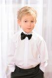 Menino louro na camisa branca com laço preto foto de stock royalty free