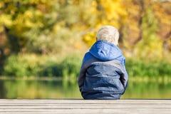 Menino louro no casaco azul que senta-se no cais do rio Vista traseira Imagens de Stock Royalty Free