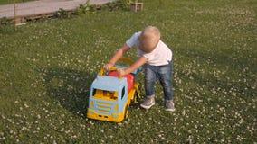 Menino louro pequeno adorável que joga com carro grande fora vídeos de arquivo
