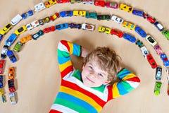 Menino louro pequeno bonito da criança que joga com lotes dos carros do brinquedo internos Imagem de Stock