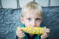 Menino louro pequeno com olhos azuis que come o milho Imagens de Stock Royalty Free