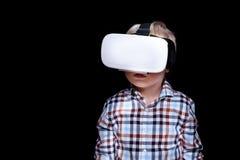 Menino louro pequeno com vidros da realidade virtual Camisa de manta Fundo preto foto de stock