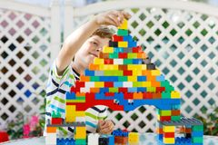 Menino louro pequeno da criança e da criança que joga com lotes de blocos plásticos coloridos Fotos de Stock