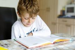 Menino louro pequeno da criança da escola que lê um livro em casa Criança interessada no compartimento da leitura para crianças L fotos de stock royalty free