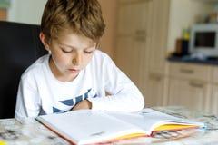 Menino louro pequeno da criança da escola que lê um livro em casa Criança interessada no compartimento da leitura para crianças L fotografia de stock
