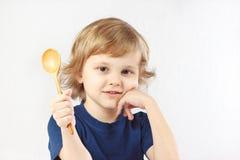 Menino louro pequeno que guardara a colher de madeira Fotografia de Stock Royalty Free