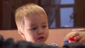 Menino louro pequeno que joga com grupo colorido da construção Gene e sua criança pequena que tem o tempo livre em casa tiro 4k video estoque