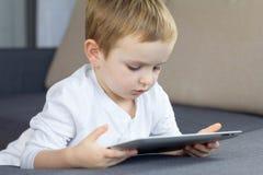 Menino louro pequeno que usa a tabuleta do écran sensível em casa Cursos da criança esperta feliz ou jogo de observação do jogo n fotografia de stock royalty free