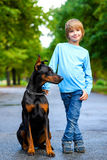 Menino louro que levanta com o cão ou o doberman dentro Fotos de Stock Royalty Free