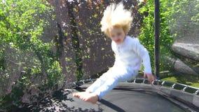 Menino louro que salta no trampolim no pátio traseiro Movimento lento vídeos de arquivo