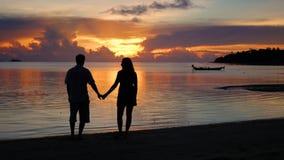 Menino loving e menina que andam na praia no tempo do por do sol silhuetas filme