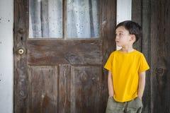 Menino melancólico da raça misturada que está na frente da porta fotos de stock