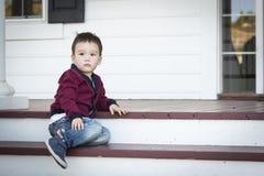 Menino melancólico da raça misturada que senta-se em Front Porch Steps imagem de stock