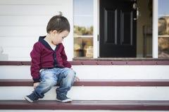 Menino melancólico da raça misturada que senta-se em Front Porch Steps fotos de stock