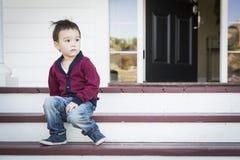 Menino melancólico da raça misturada que senta-se em Front Porch Steps fotografia de stock royalty free