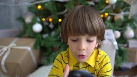 Menino muito bonito adorável que senta-se no fundo da árvore de Natal e que joga com smartphone Lento-movimento Criança vídeos de arquivo